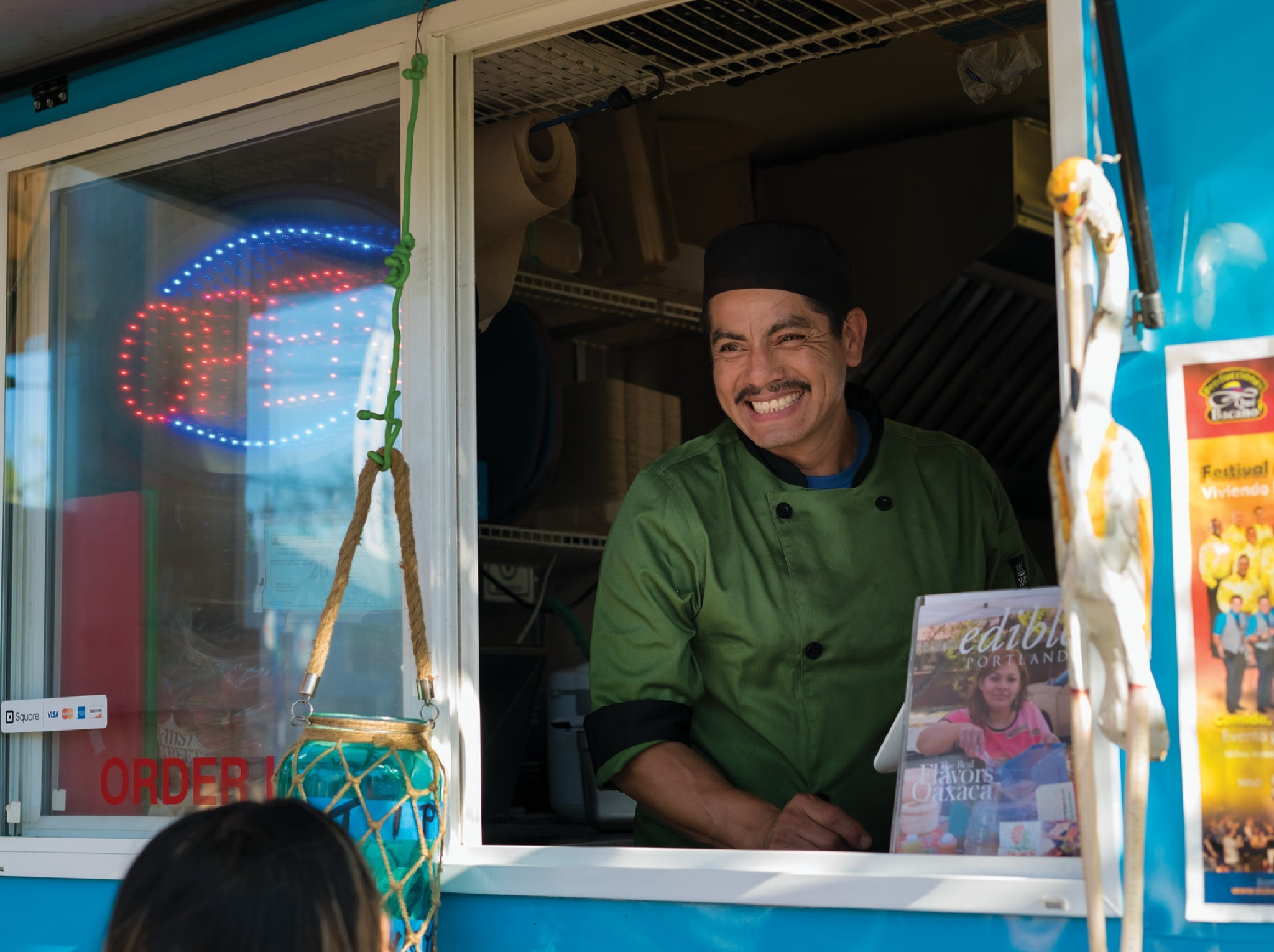 A chef smiling out the window of a food truck
