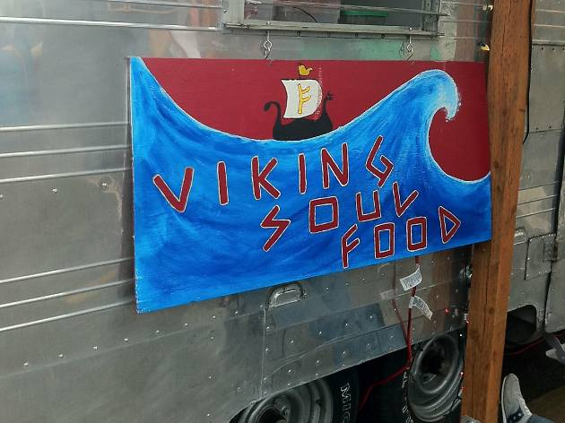 A sign with a wave and Viking ship that reads Viking Soul Food