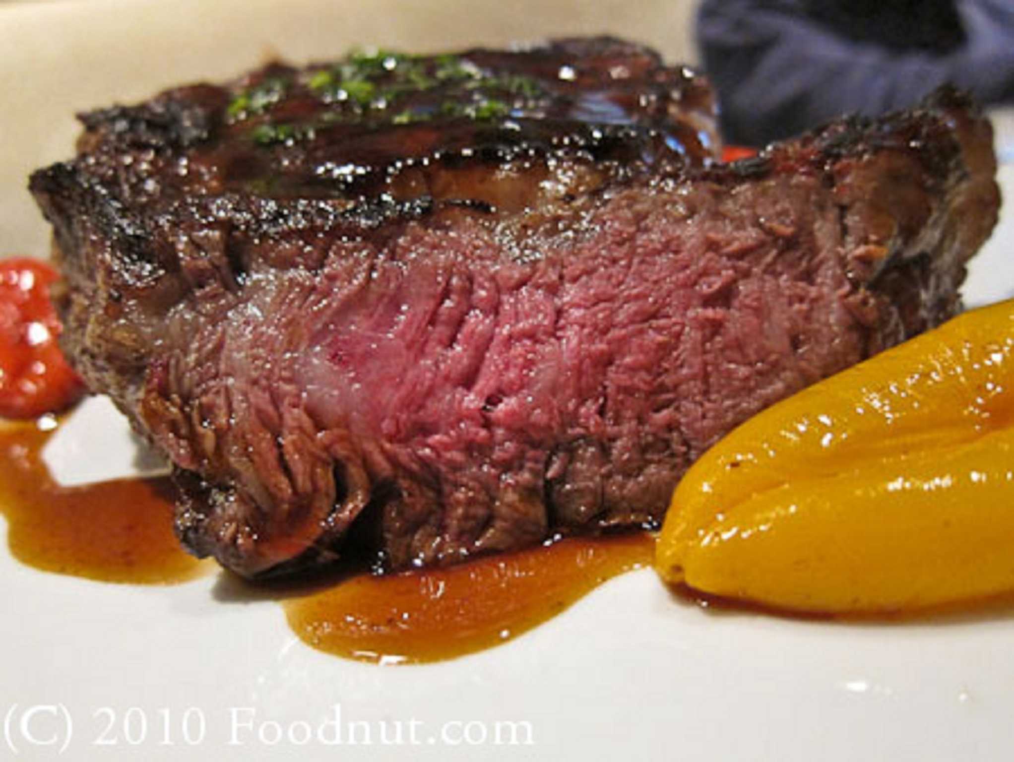 A steak next to a roasted pepper