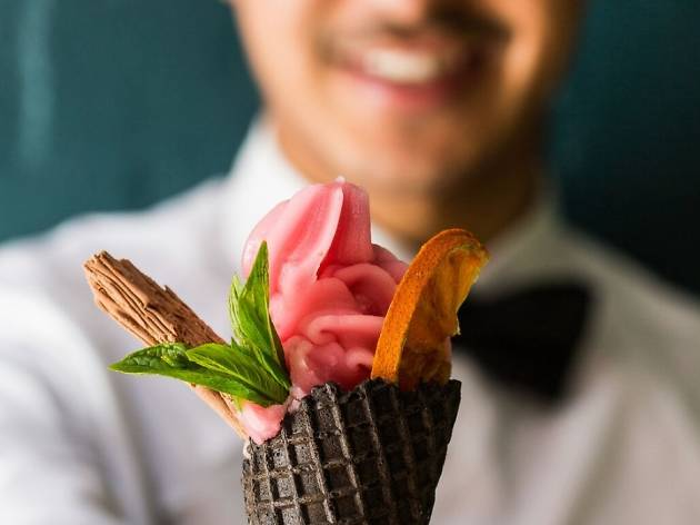 A smiling person wearing a bowtie holds out a soft serve cone.