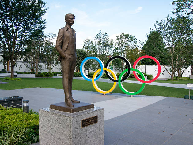 Olympic rings and statue of Pierre de Coubertin near the new national stadium in Tokyo