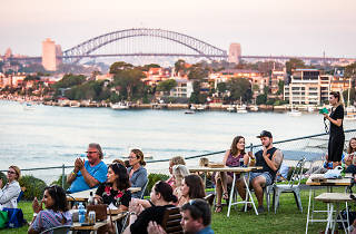 People sitting at tables on Cockatoo Island with the Sydney Harbour Bridge in the background.