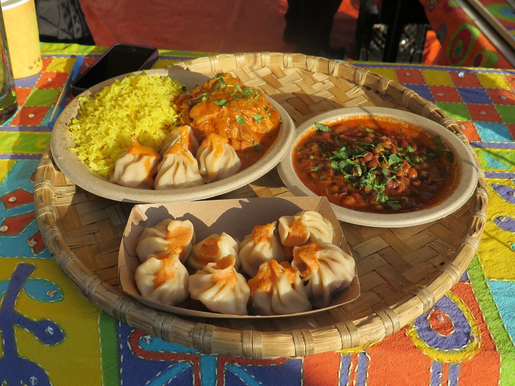A tray with different plates of dumplings and curries on a colorful table cloth