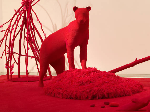 An installation of a red crocheted bear standing on a matching red crocheted landscape