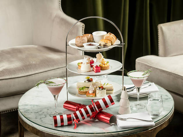 A Christmas-themed high tea on a three-tier stand on a coffee table