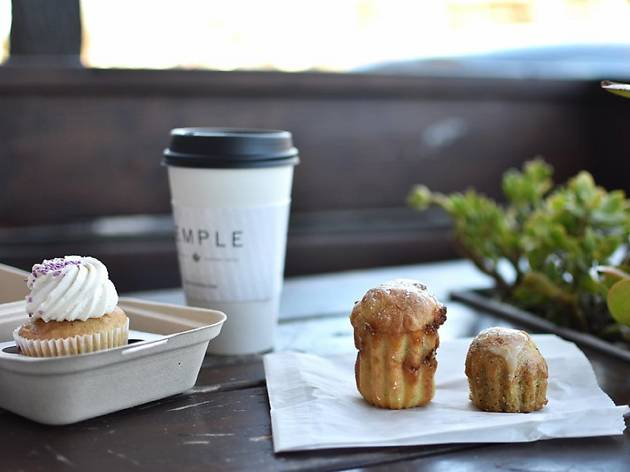 A table with a coffee to-go cup and pastries