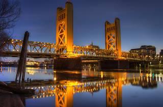 The Sacramento bridge and waterfront still lit up at sunrise
