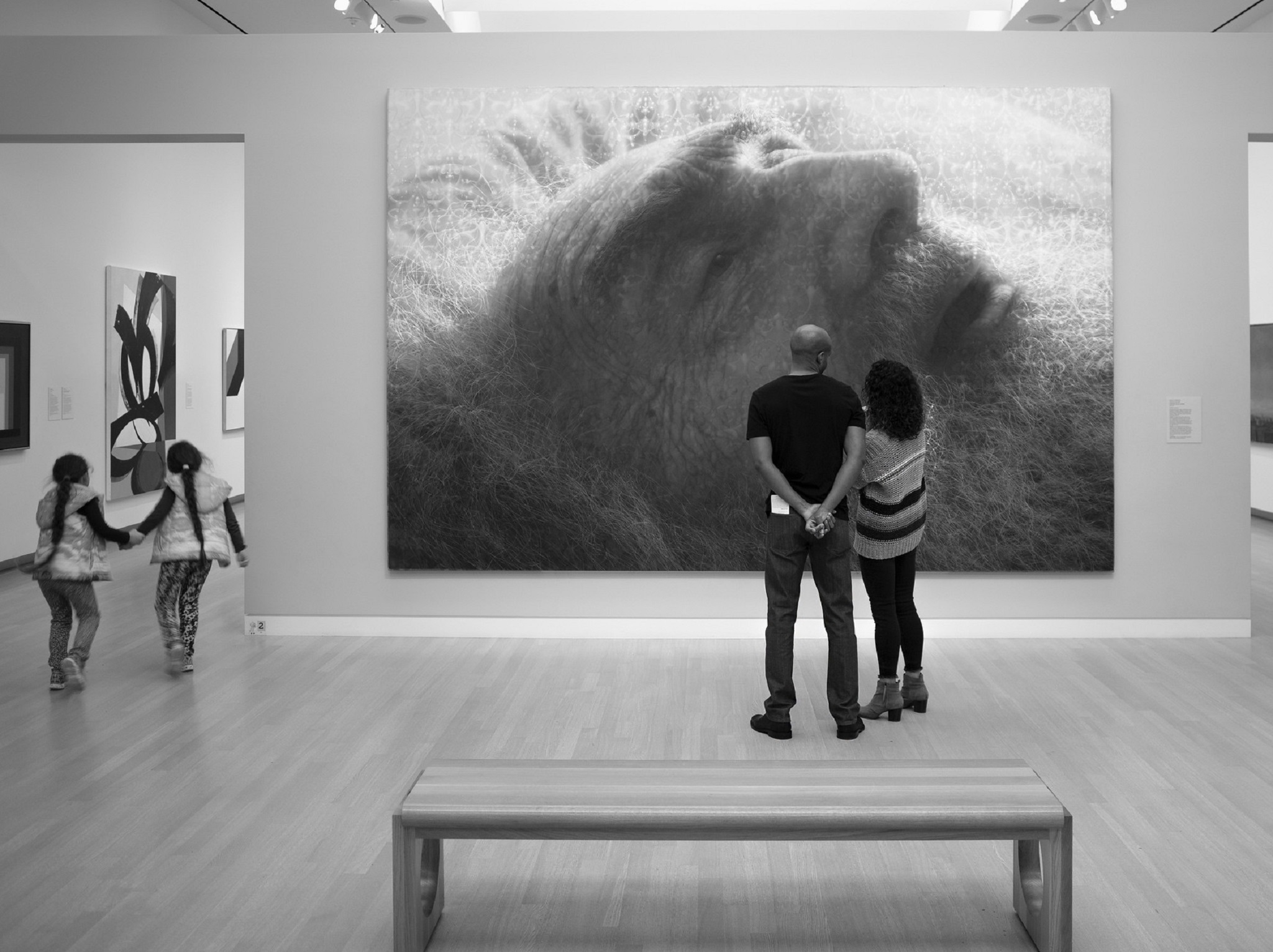 Two people standing in front of a painting at the museum