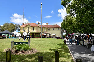 A large old style building sits amongst green lawns, market stalls are off to the right.