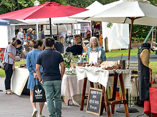 People browse outdoor market stalls.