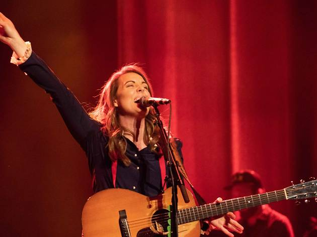 Brandi Carlile sings into a microphone with her hand in the air, she is holding a guitar.