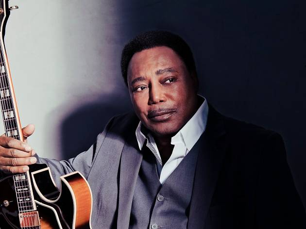 George Benson poses with his guitar in a grey suit.