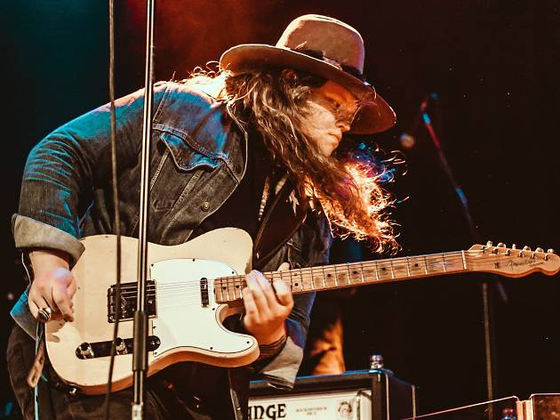 A man with long hair and a hat is mid guitar solo.