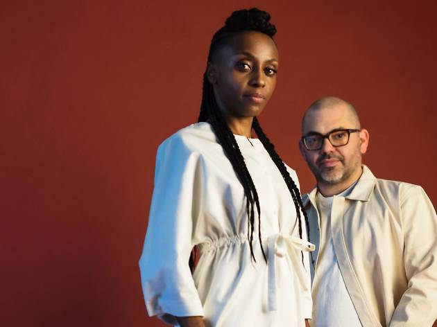 Two people stare down the camera, they are wearing white against a red wall.