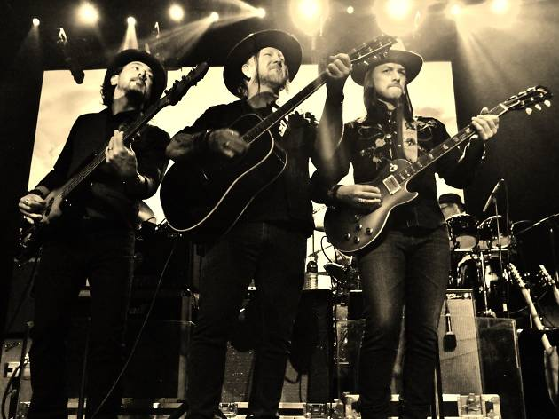 A trio of musicians pose on stage with guitars, they wear cowboy hats.
