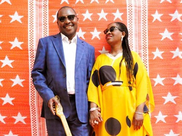 Two people in colourful outfits and sunglasses pose in front of a red wall with starts.