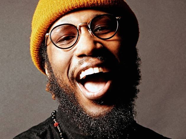 Cory Henry laughs at the camera, he has a beard and is wearing a yellow beanie.