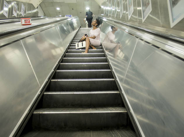 Babycakes Romero: woman sits on escalator