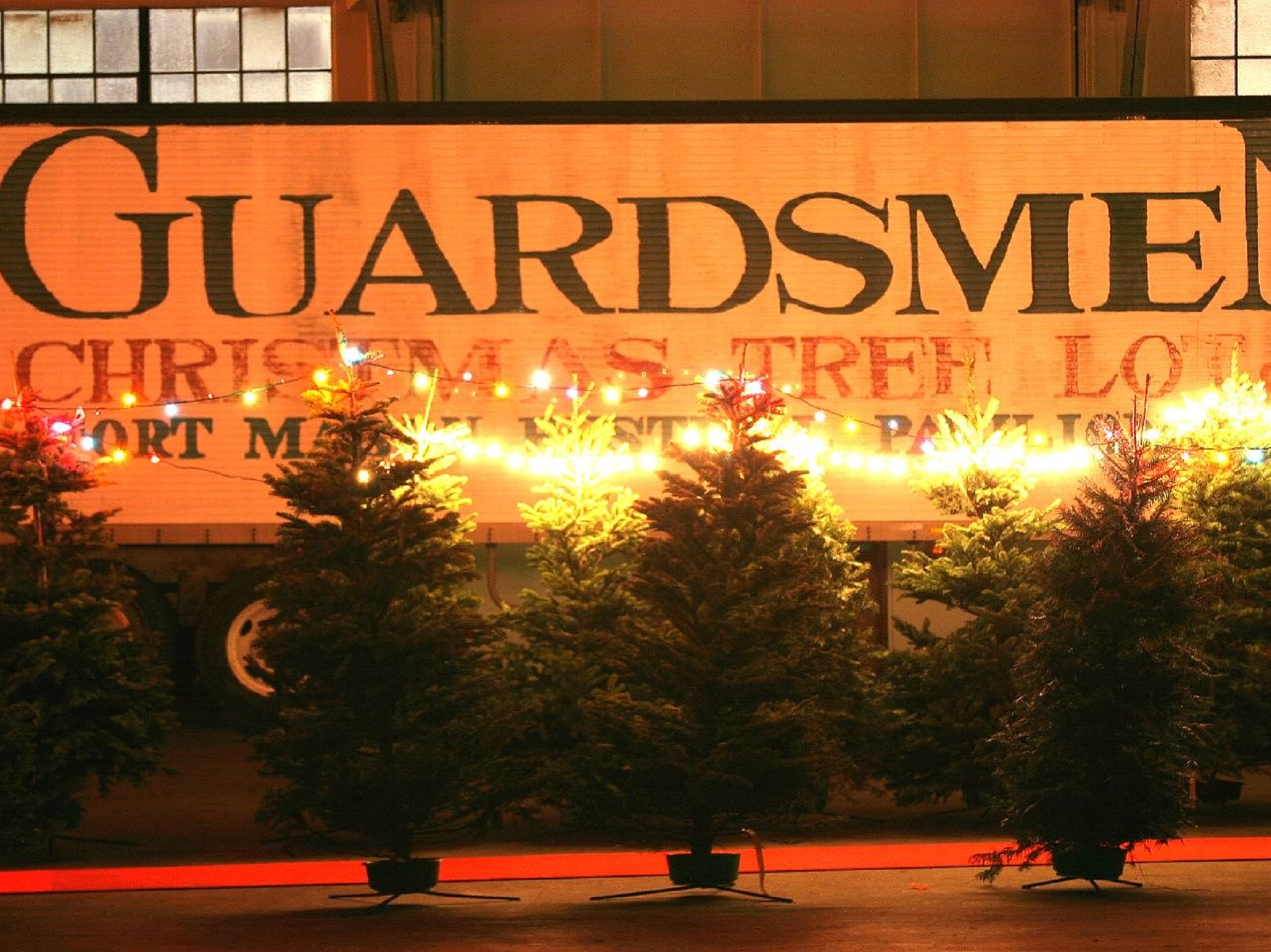 The sign for the Guardsmen lot with trees in front