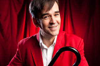 Press shot of comedian Tim Ferguson in a red suit and cane