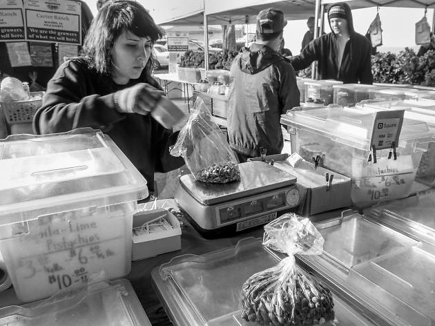 A woman scooping nuts in a black and white photo