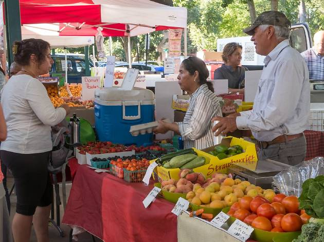 Two vendors selling vegetables and a woman speaking to them