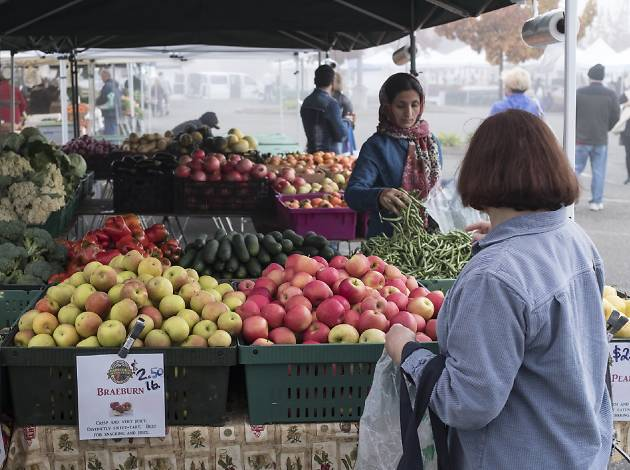 A farmers market stall filled with produce and two women shopping
