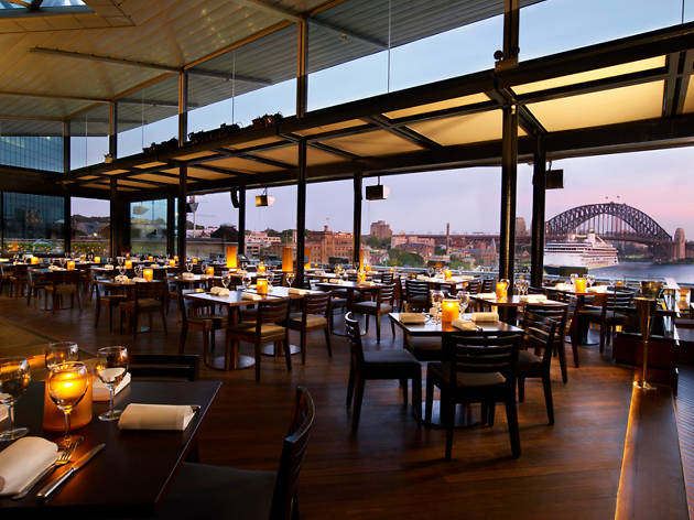 A restaurant full of tables with wine glasses and candles overlooks Sydney Harbour.