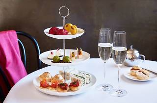Three tiers of high tea snacks on a table with two glasses of Champagne