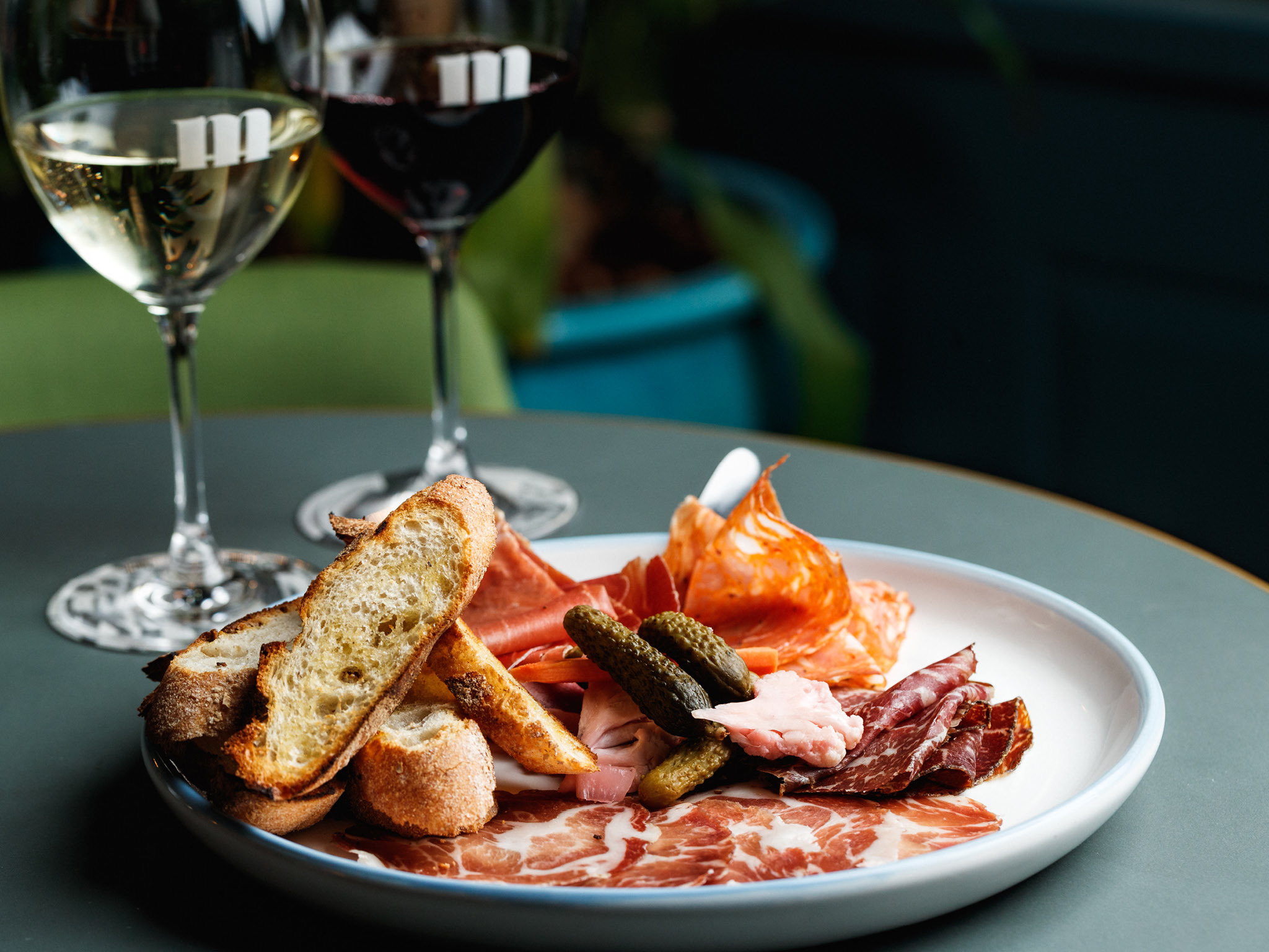 A plate of cured meats and nibbles with a glass of wine.