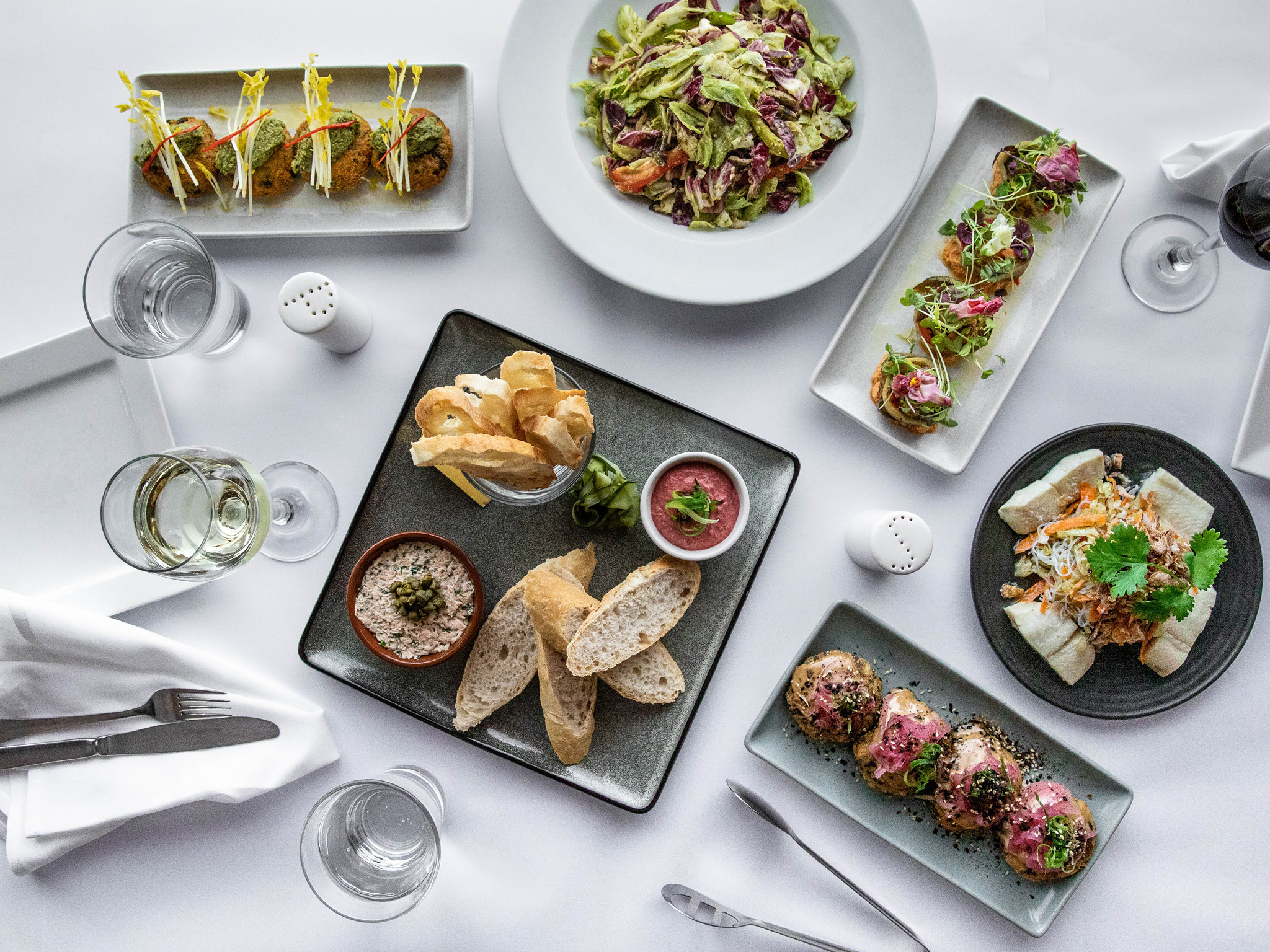 A table of tapas dishes on a white table cloth.