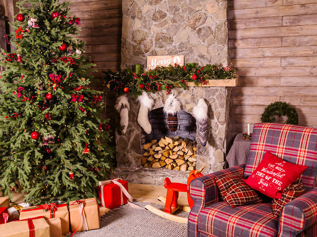 Christmas tree in cabin room with armchair, presents and fireplace