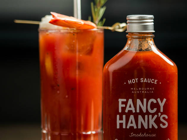 Bottle of hot sauce next to a Bloody Mary cocktail
