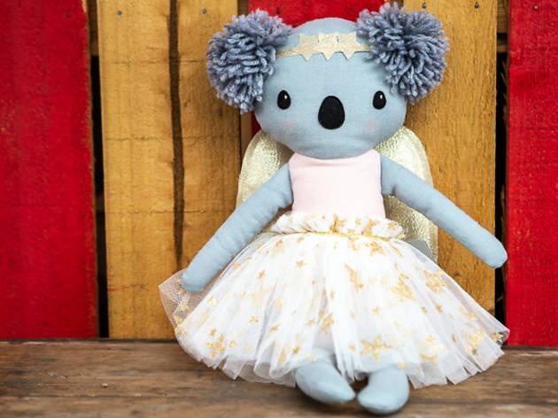 A soft koala doll wearing a tutu and angel wings