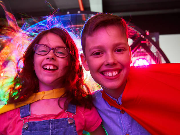 Two kids lit by coloured lights