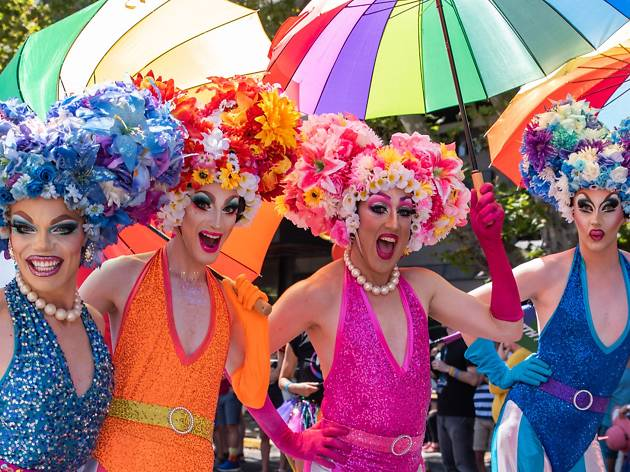 Four drag queens in bright outfits and flowery wigs pose with umbrellas.