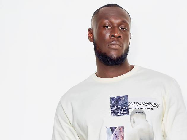 Rapper Stormzy stares down the camera in a white t-shirt.