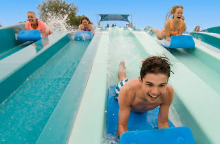 Three people racing down a waterslide on foam mats