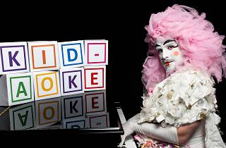 A performer in elaborate pink wig and white makeup plays a grand piano.