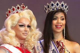 A drag queen and a beauty queen pose with crowns.