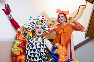 Two drag queens pose in a stairwell, Miss 3D wears a headpiece made of retro 3D cardboard glasses and Etcetera Etcetera wears all orange with a big bow on her head.