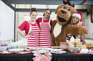 Three people in striped red aprons pose with a giant reindeer.