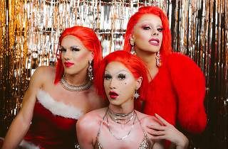 Three drag queens dressed in red festive outfits pose in front of a gold tinsel curtain.