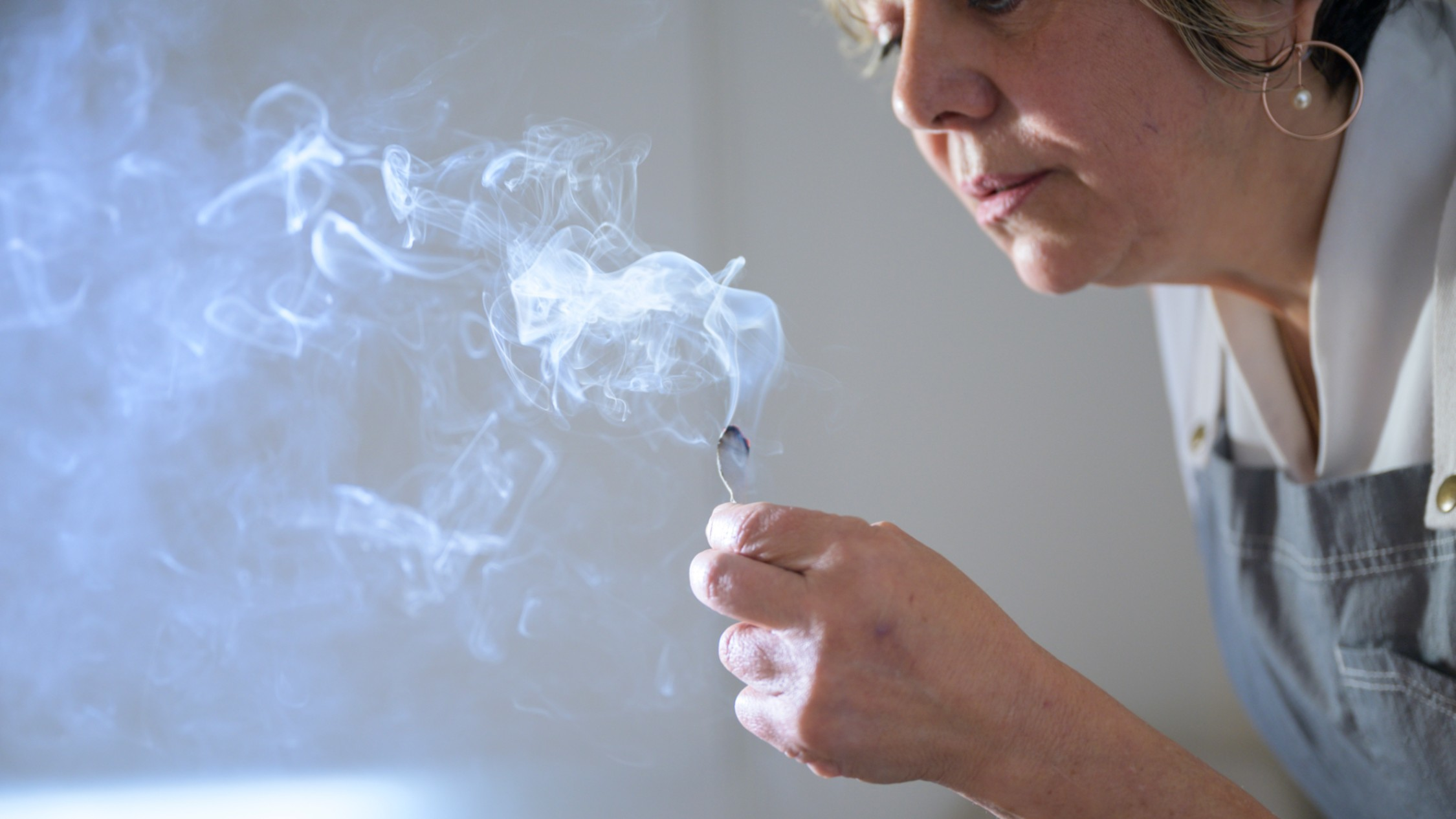 A beauty therapist gently blows on a smoking piece of sage or similar herb.