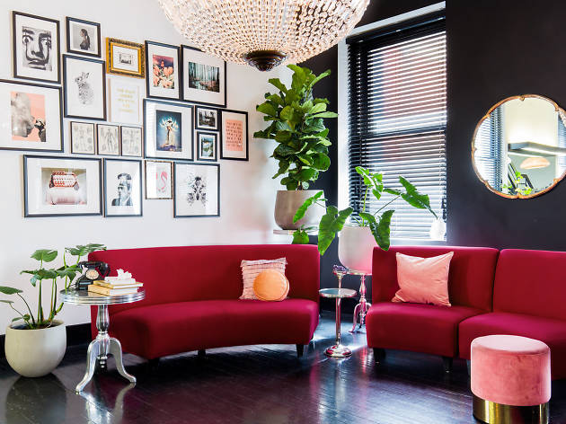 A luxe looking room with red lounges, pink cushions, and framed photos.