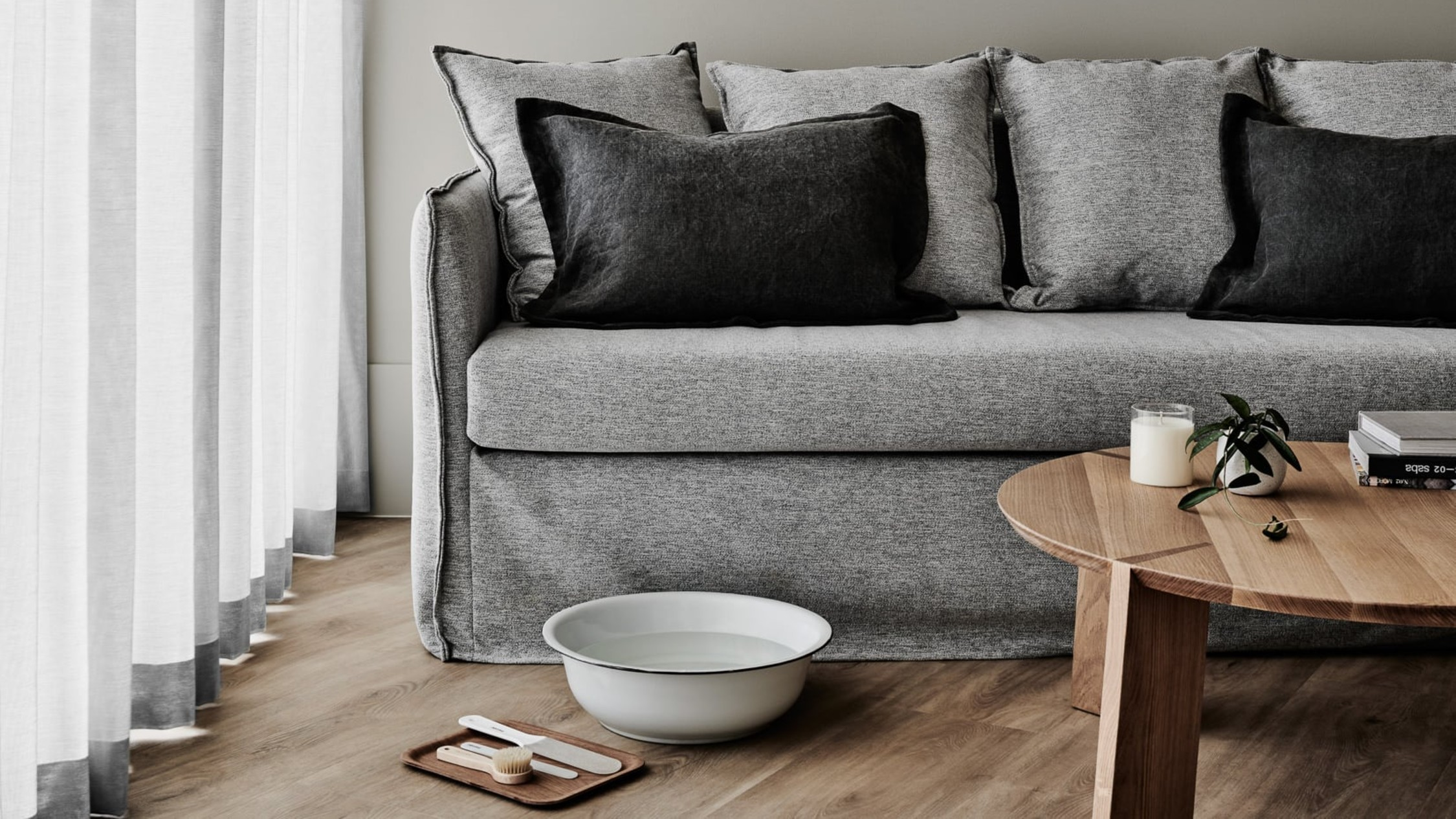A large bowl and pedicure supplied sit infront of a grey couch.