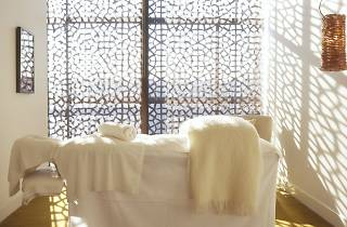 A  massage bed with white bedding and towels in front of a brightly lit window.