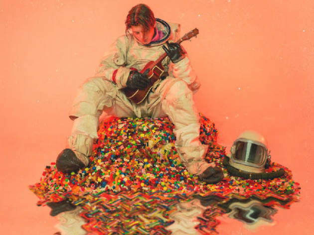 Ruel pictured in a spacesuit with a guitar on a pile of lollies
