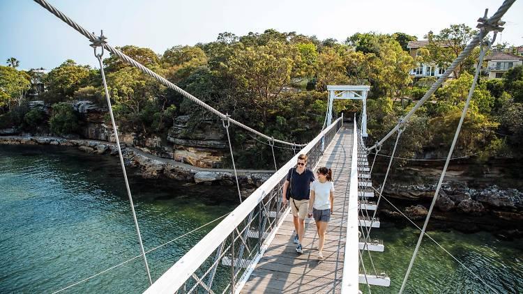Two people walk across a suspension bridge over water.