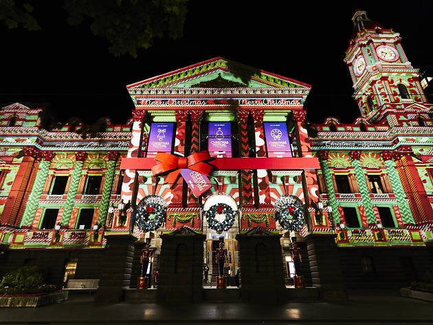 Melbourne Town Hall at night, covered in wreaths, a giant red bow ad festive projection art